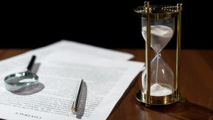 Document and hourglass on table